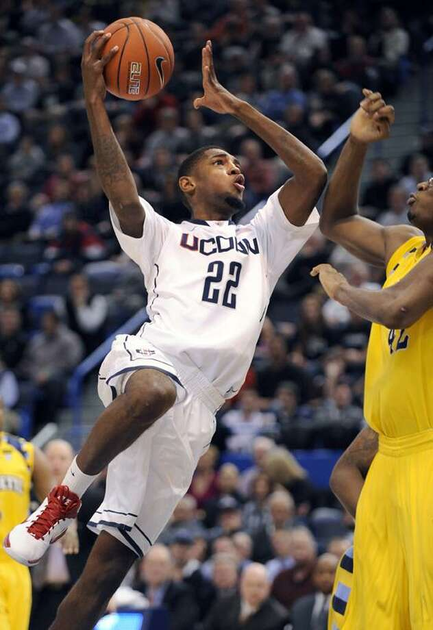 AP Connecticut's Roscoe Smith, left, drives past Marquette's Chris Otule during the first half of an NCAA college basketball game in Hartford on Thursday.