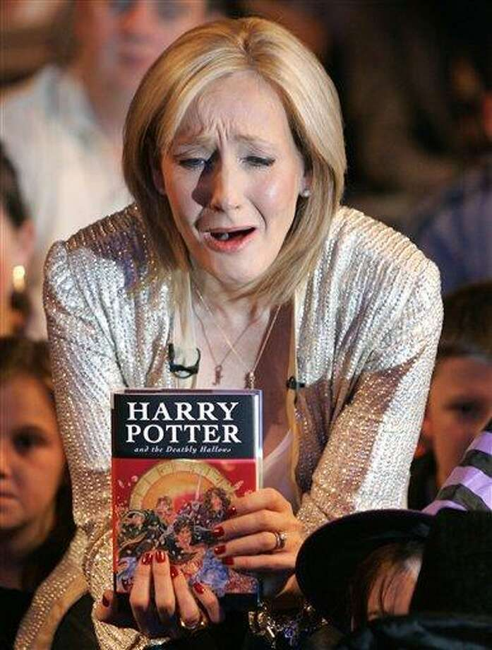 """In this Friday, July 20, 2007 file picture British author J.K. Rowling reacts during a photocall for the release of her latest Harry Potter book titled """"Harry Potter and the Deathly Hallows"""" at the Natural History Museum in London.Harry Potter fans are holding their collective breath as author J.K. Rowling gets set to reveal her latest project involving the boy wizard. Rowling has called a news conference Thursday in London to reveal details of """"Pottermore,"""" a mysterious website that has been taunting fans with the words """"coming soon."""" (AP Photo/Kirsty Wigglesworth) Photo: ASSOCIATED PRESS / AP"""