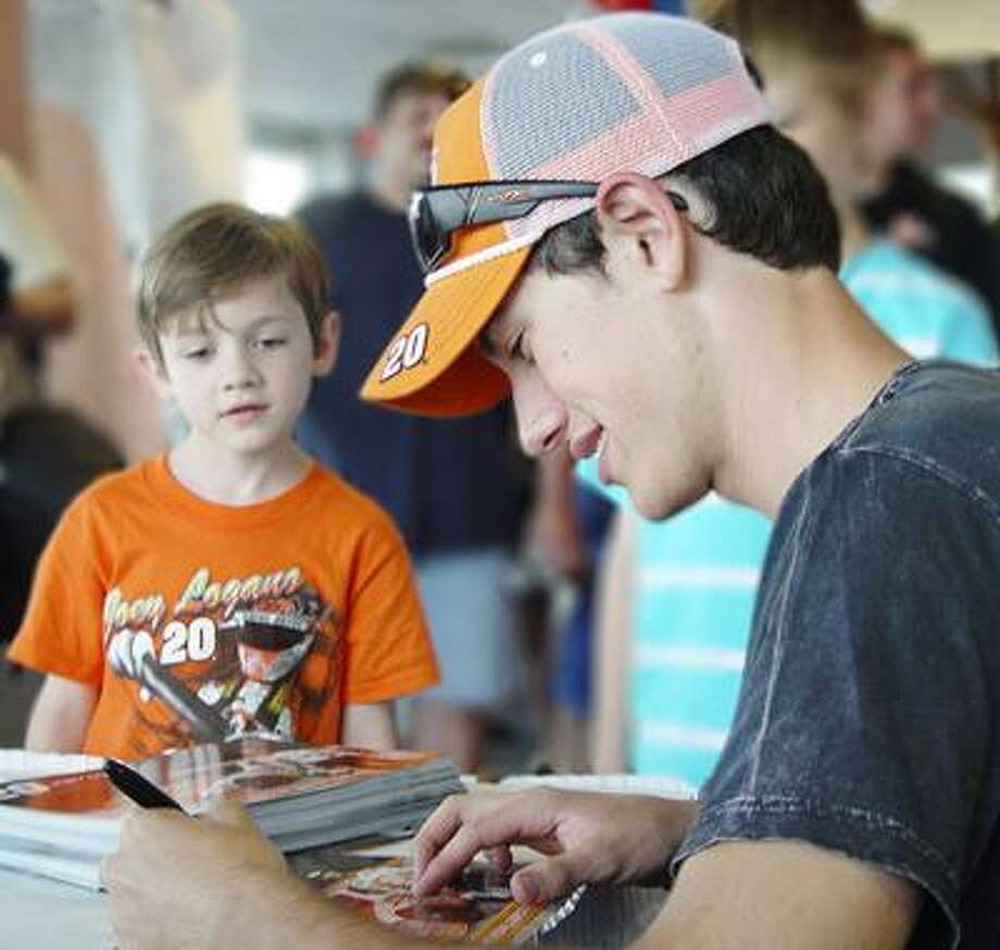 NASCAR driver Joey Logano autograph's a photo as a young fan looks on Wednesday at Toyota of Wallingford.(Jake Grossman /Special to the Press)
