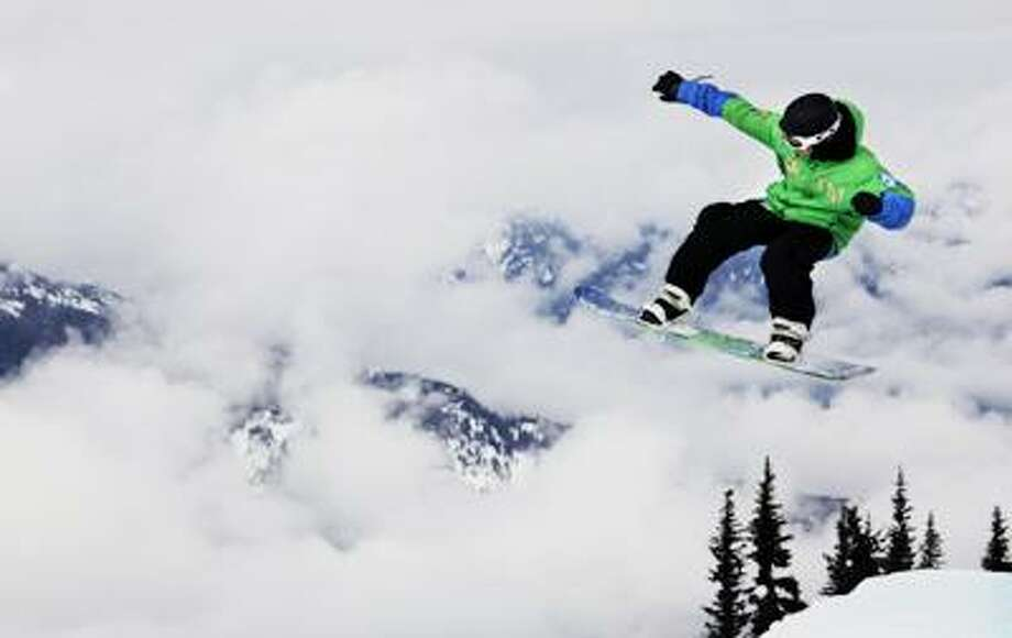 A snowboarder flies through the air as he goes down Mount Blackcomb in Whistler, British Columbia, Monday. (Associated Press) Photo: AP / AP