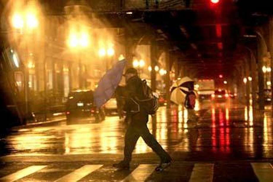 Pedestrians fight high winds and rain along East Madison Street and southbound Wabash Avenue in Chicago's Loop on Tuesday, Oct. 26, 2010. Strong wind and torrential rain buffeted the Midwest Tuesday as forecasters predicted the giant storm could be the most powerful to hit Illinois in over seven decades. (AP Photo/Chicago Tribune, Nancy Stone) THE NEW YORK TIMES OUT, CHICAGO LOCALS OUT, ROCKFORD REGISTER STAR OUT, MAGS OUT, NO SALES, TV OUT, ONLINE OUT Photo: AP / Chicago Tribune