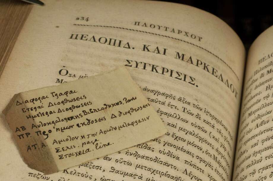 In this photo provided Tuesday, by Washington University in St. Louis, shows a scrap of paper with Greek notes scholars say was written by Thomas Jefferson and found tucked in a volume of Plutarch's Lives. The book is one of dozens owned by Thomas Jefferson that have been found in the rare books collection at the St. Louis school.  The books were among about 3,000 that were donated to the school in 1880 after the death of Jefferson's granddaughter, Ellen Wayles Randolph Coolidge, and her husband, Joseph Coolidge. (AP Photo/Washington University, Joe Angeles) Photo: AP / Washington University