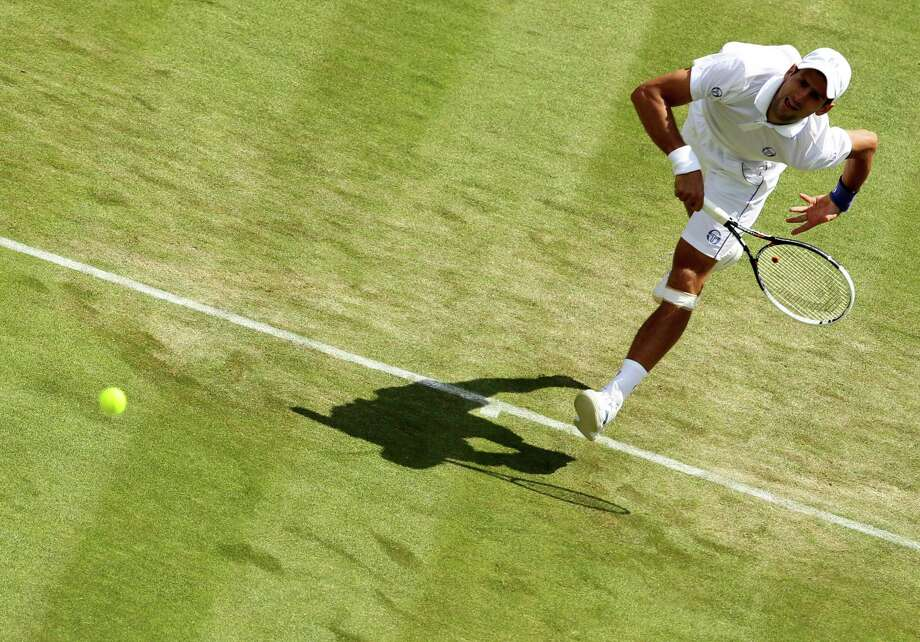 Tennis - 2011 Wimbledon Championships - Day Four - The All England Lawn Tennis and Croquet Club. Serbia's Novak Djokovic in action during his match against South Africa's Kevin Anderson on day four of the 2011 Wimbledon Championships at the All England Lawn Tennis and Croquet Club, Wimbledon. URN:11033002 (Press Association via AP Images) Photo: Associated Press / EMPICS Sport2011