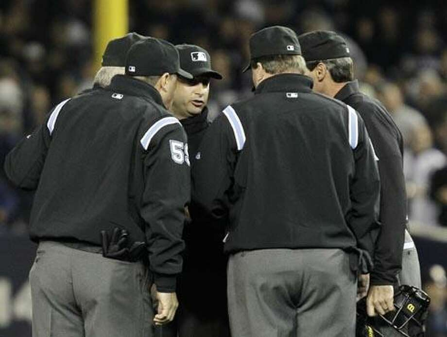 Umpires huddle after an apparent home run by New York Yankees' Lance Berkman in the second inning of Game 4 of baseball's American League Championship Series against the Texas Rangers Tuesday, Oct. 19, 2010, in New York. After review, it was ruled a foul ball. (AP Photo/Kathy Willens) Photo: AP / AP