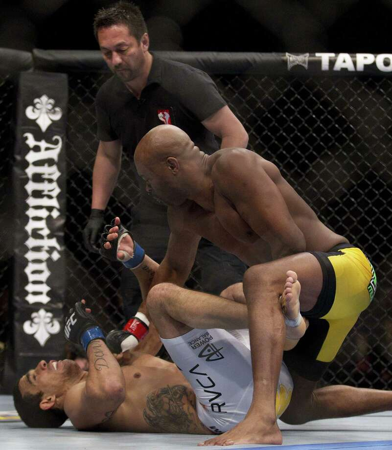 Anderson Silva, right, finishes off Vitor Belfort to win by knockout in the first round of a middleweight title UFC 126 mixed martial arts bout, Saturday, Feb. 5, 2011, in Las Vegas. (AP Photo/Julie Jacobson) Photo: ASSOCIATED PRESS / AP2011