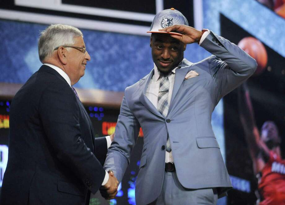 NBA Commissioner David Stern, left, poses with Connecticut's Kemba Walker, whom the Charlotte Bobcats selected with the ninth pick in the NBA basketball draft Thursday, June, 23, 2011, in Newark, N.J. (AP Photo/Bill Kostroun) Photo: ASSOCIATED PRESS / AP2011