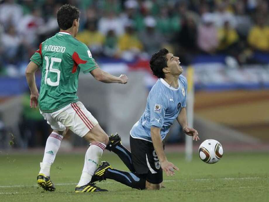 Mexico's Hector Moreno, left, challenges Uruguay's Luis Suarez, right, during the World Cup group A soccer match between Mexico and Uruguay at Royal Bafokeng Stadium in Rustenburg, South Africa, on Tuesday. (AP) Photo: ASSOCIATED PRESS / AP