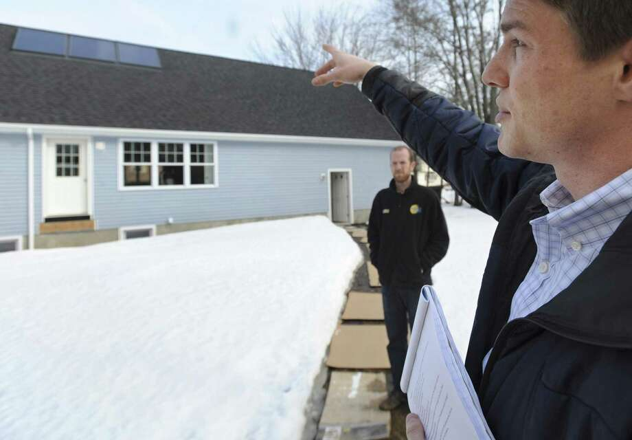 In this photo from Thursday, Tommy Cleveland, right, solar testing laboratory manager from the University of New Haven,  gestures toward solar panels during a visit to Glen Mirmina's home as Joey Dorwart from Sunlight Solar Energy company, looks on, in Milford, Conn. The University of New Haven is expected to become an accredited testing lab for solar thermal products, reducing certification delays and boosting interest in solar thermal energy as an alternative to oil, natural gas and electricity. (AP Photo/Jessica Hill) Photo: ASSOCIATED PRESS / AP2011
