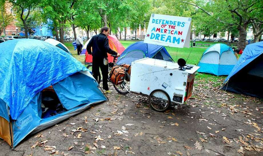 Kenneth Manteau of Branford maneuvers his bicycle through tents at the Occupy New Haven protest on the New Haven Green. Arnold Gold/Register
