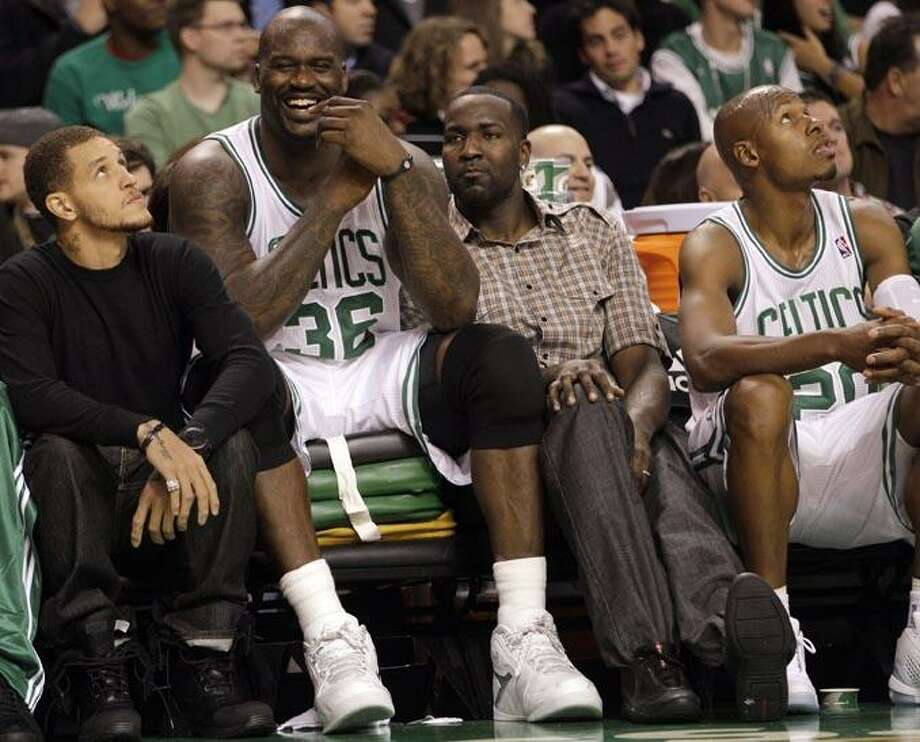 Boston Celtics' Shaquille O'Neal (36) sits on a pile of cushions as he talks with teammates Delonte West, left, and Kendrick Perkins, second from right, during the first half of an NBA preseason basketball game against the New Jersey Nets in Boston, Wednesday, Oct. 20, 2010. At right is Ray Allen. (AP Photo/Mary Schwalm) Photo: AP / FR158029 AP