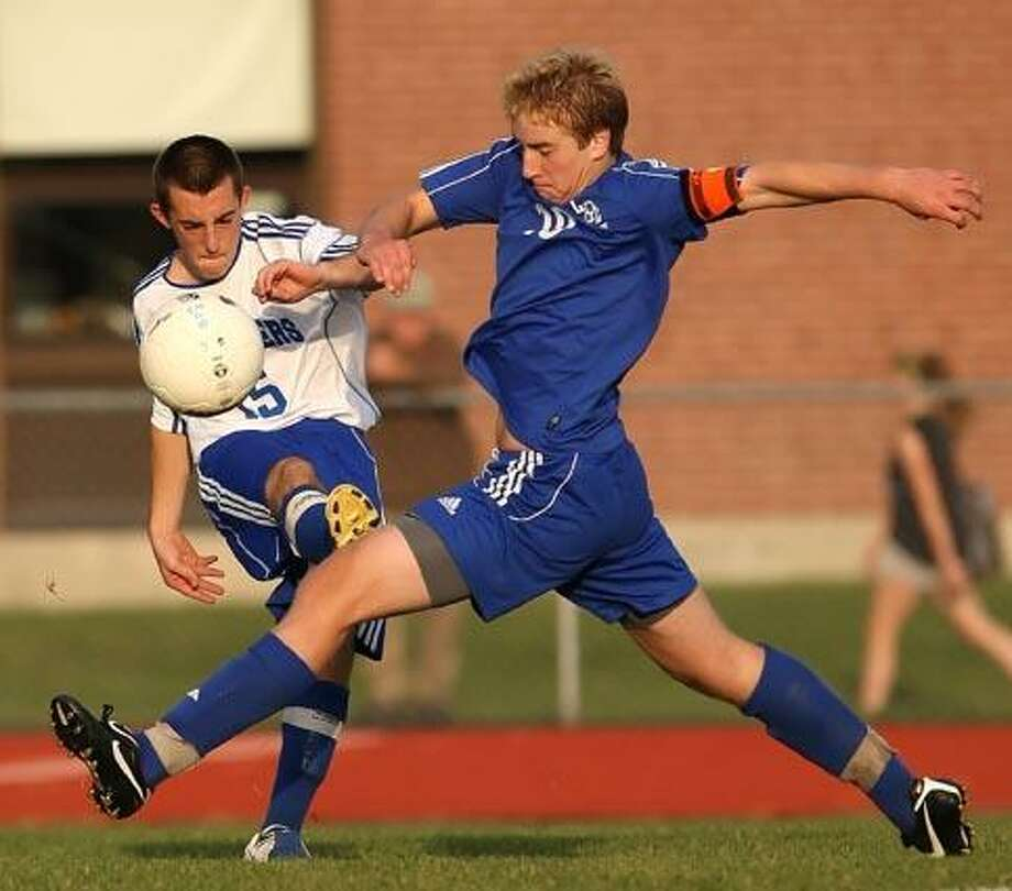 Old Lyme's Pat Hallahan, right, lunges for the ball in a game against East Hampton Monday. (Todd Kalif