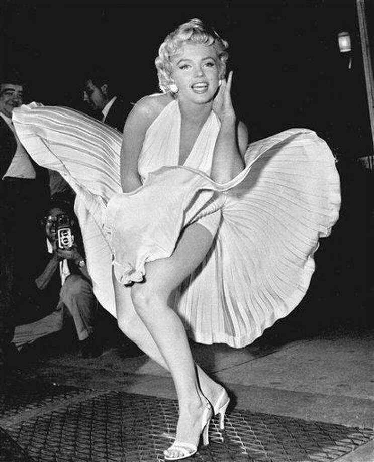 "In this Sept. 9, 1954 file photo, Marilyn Monroe poses over the updraft of a New York subway grating while in character for the filming of ""The Seven Year Itch"" in New York. Monroe's flirty dress from ""The Seven Year Itch"" is going to a collector who bid $4.6 million at a weekend auction of Hollywood memorabilia. The dress was among the film costumes and props collected by Debbie Reynolds over four decades.  (AP Photo/Matty Zimmerman, File) Photo: AP / AP1954"