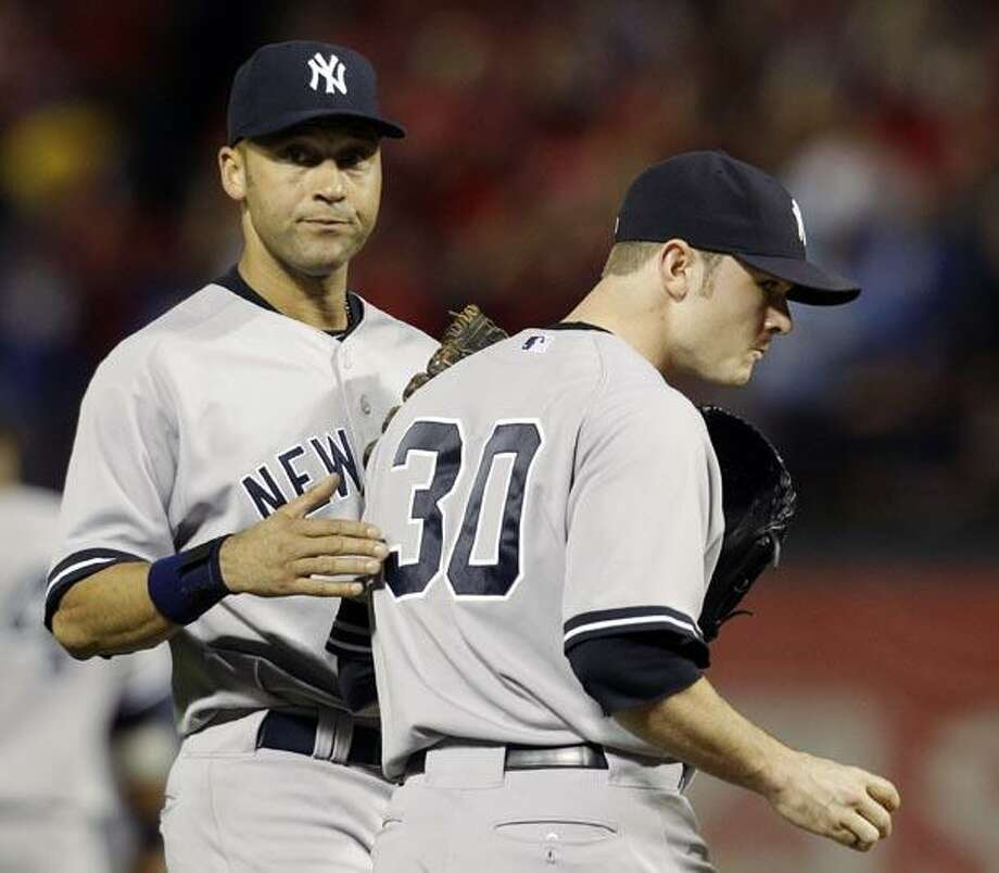 New York Yankees shortstop Derek Jeter, left, tries to calm relief pitcher David Robertson after Robertson gave up a two-run home run to Texas Rangers' Nelson Cruz in the fifth inning of Game 6 of baseball's American League Championship Series Friday in Arlington, Texas. (AP Photo/Tony Gutierrez) Photo: AP / AP