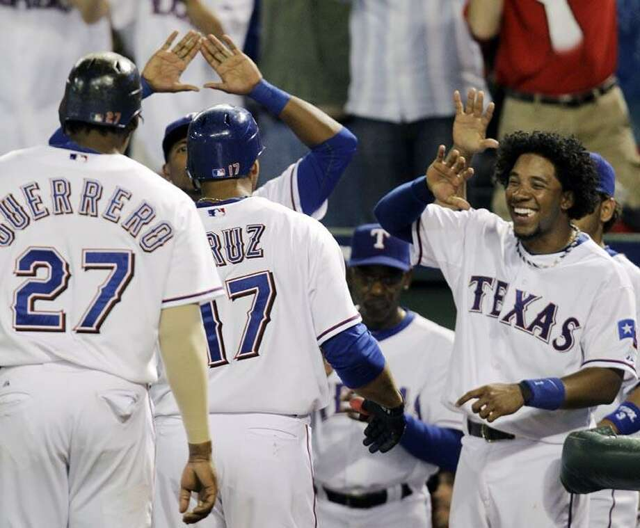 Texas Rangers' Elvis Andrus, right, greets Nelson Cruz (17) and Vladimir Guerrero (27) after Cruz's two-run home run against the New York Yankees in the fifth inning of Game 6 of baseball's American League Championship Series Friday in Arlington, Texas. (AP Photo/Tony Gutierrez) Photo: AP / AP
