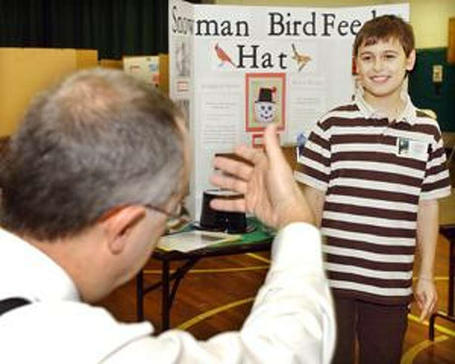 The Middletown Press) Tyler J. Beaulieu, a fourth-grade student at Center School, demonstrates to judges how his invention, the Handsfree Umbrella, works.