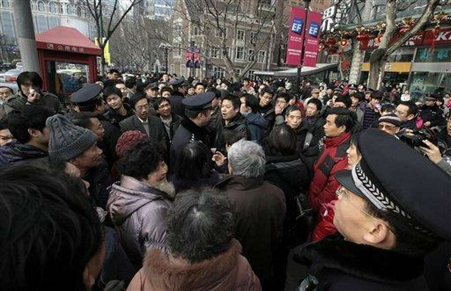 "Police officers urge people to leave as they gather in front of a cinema that was a planned protest site in Shanghai, China, Sunday, Feb. 20, 2011. Jittery Chinese authorities staged a show of force Sunday to squelch a mysterious online call for a ""Jasmine Revolution"" apparently modeled after pro-democracy demonstrations sweeping the Middle East. (AP Photo/Eugene Hoshiko) Photo: ASSOCIATED PRESS / AP2011"