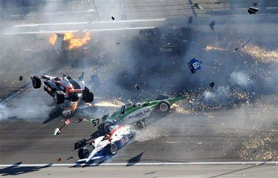 Drivers crash during a wreck that involved 15 cars during the IndyCar Series' auto race at Las Vegas Motor Speedway in Las Vegas on Sunday, Oct. 16, 2011. Wheldon was airlifted to a hospital. Will Power (12), of Australia, is airborne at left. (AP Photo/Las Vegas Review-Journal, Jessica Ebelhar) LAS VEGAS SUN OUT  MANDATORY CREDIT Photo: AP / Las Vegas Review-Journal