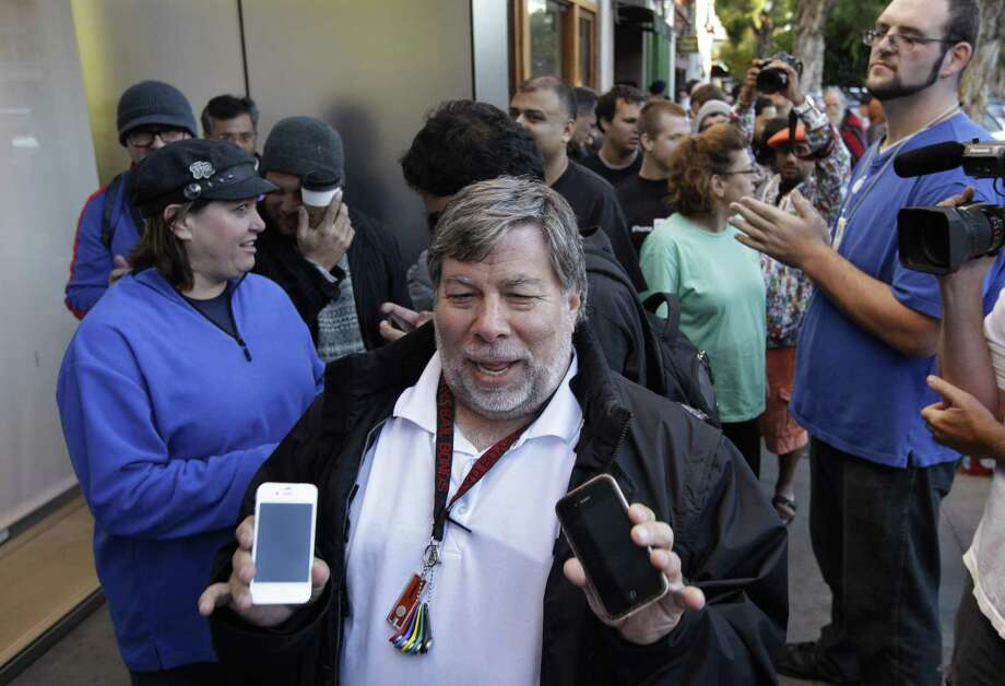 Apple co-founder Steve Wozniak holds up two of his old Apple iPhone 4 as he waits in line at the Apple store in Los Gatos, Calif. Friday. Wozniak waited 20 hours in line to be the first Apple customer at the Los Gatos Apple store to buy the new iPhone 4S. (AP Photo/Paul Sakuma) Photo: AP / AP