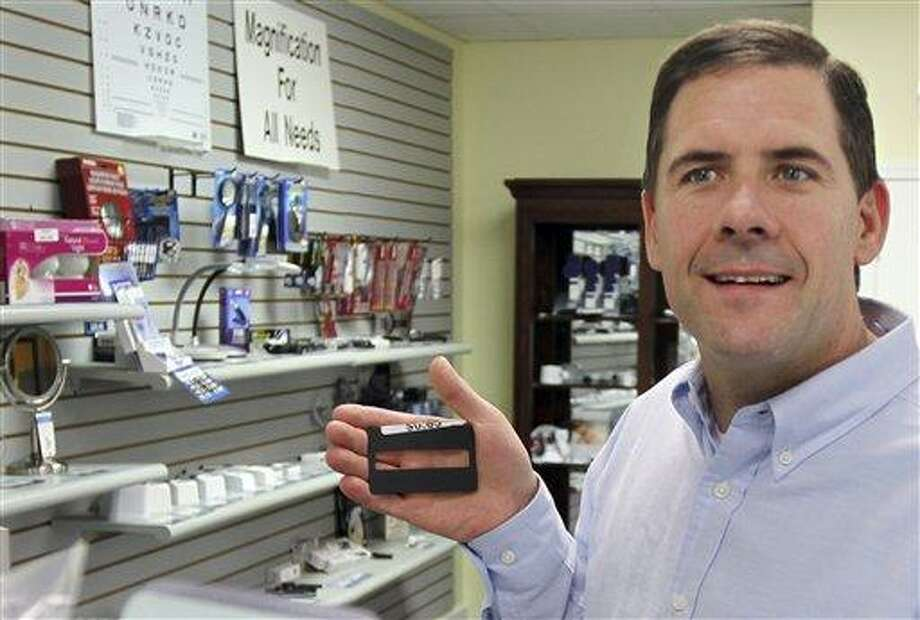 In this June 7, 2011 photo, Charlie Collins holds a signature guide card at his store, Vision Dynamics, in Cheshire, Conn. Collins, legally blind since age 13, runs a shop that sells devices that helps expand the lives of people with visual impairments. (AP Photo) Photo: AP / Waterbury Republican-American