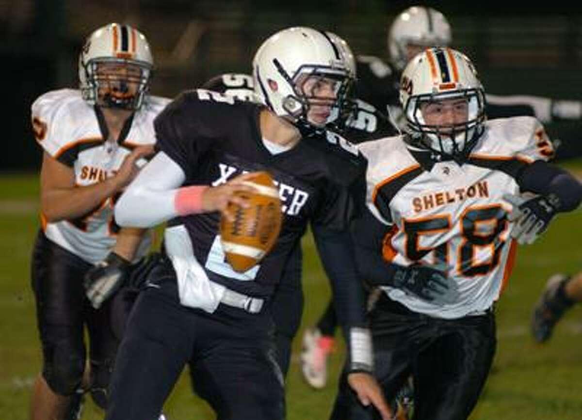 Xavier quarterback Pat D'Amato runs past Shelton's Ricky Raffaele (58) Friday night at Palmer Field. (Matt Jacques