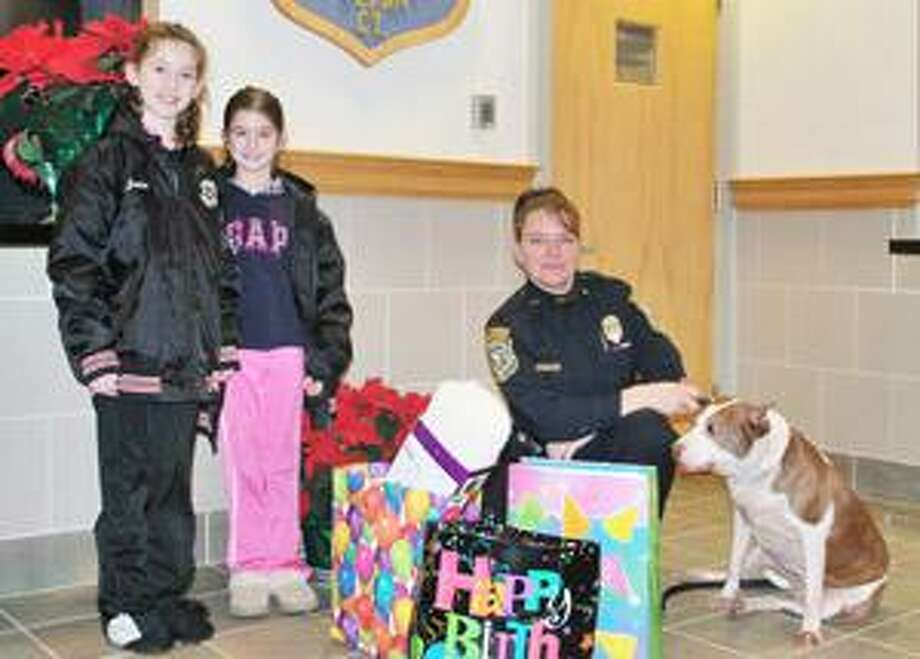 (Contributed photo) Jessica and Caitlin Della Ratta, 8-year-old twins, of Cromwell, decided that, since their birthday falls so close to Christmas, they would like to help out others. Both girls chose a local charity and, in lieu of gifts for themselves, at their birthday party the two asked for donations. Caitlin's charity was to help the Cromwell Animal Shelter. Pictured left to right are Jessica Della Ratta, Caitlin Della Ratta, Cromwell Animal Control Officer Cheryl Gagnon and Trixie, a pit bull up for adoption.
