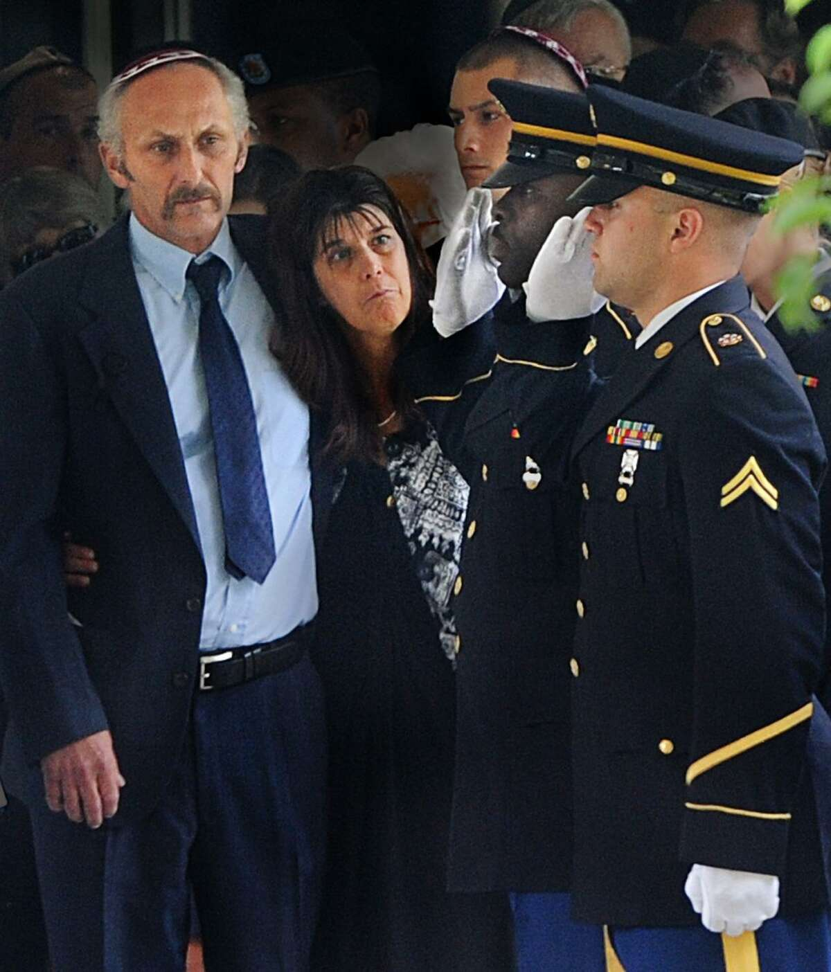 Michael and Donna Soufrine, parents of PFC Eric Soufrine, watch as pall bearers salute after placing Soufrine's casket in the hearse. PFC Soufrine of Woodbridge was killed in Afghanistan. Melanie Stengel/Register