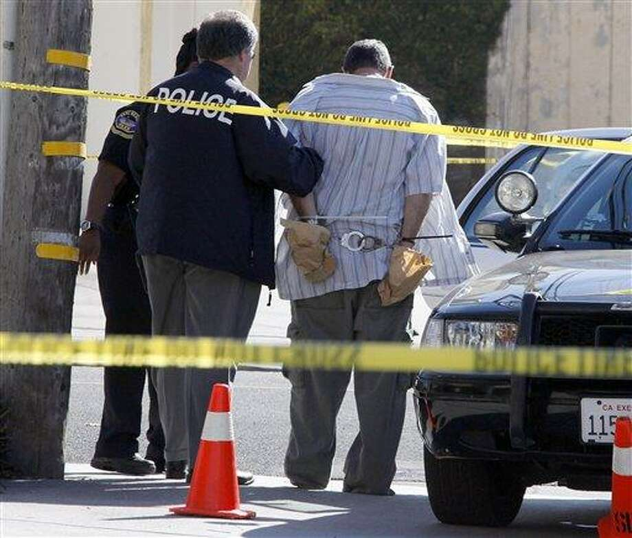Police officers stand with a man who was being held in a patrol car at the scene of the arrest of a suspect near the Salon Meritage in Seal Beach, Calif., where a shooting left eight people dead and one critically injured Wednesday, Oct. 12, 2011.  (AP Photo/Reed Saxon) Photo: AP / 2011 AP