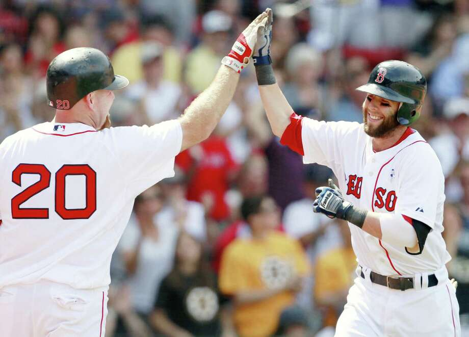 Boston Red Sox's Dustin Pedroia, right, celebrates his solo home run with teammate Kevin Youkilis in the fourth inning of an interleague baseball game against the Milwaukee Brewers in Boston, Sunday, June 19, 2011. The Red Sox won 12-3. (AP Photo/Michael Dwyer) Photo: ASSOCIATED PRESS / AP2011