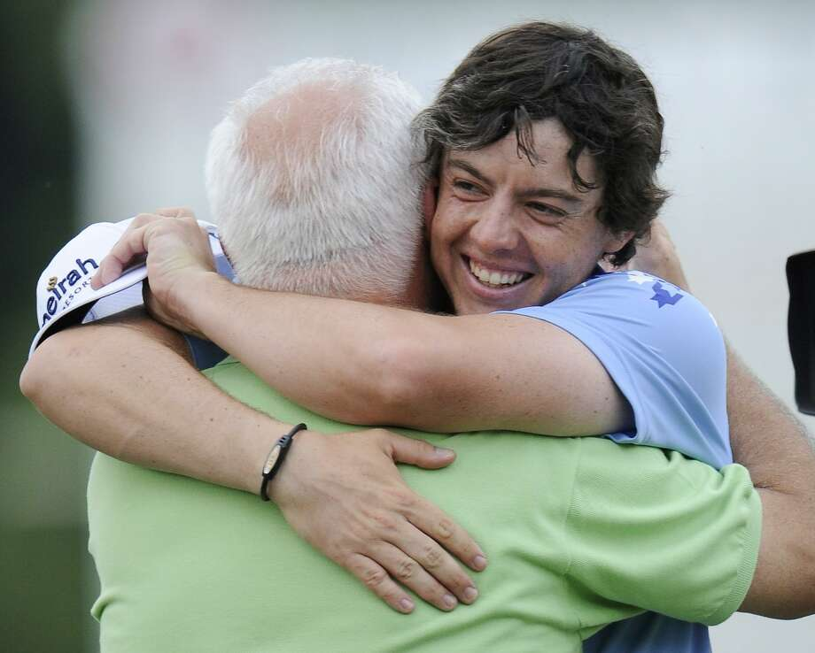 Rory McIlroy hugs his father Gerry on the 18th green after winning the U.S. Open Championship golf tournament in Bethesda, Md., Sunday, June 19, 2011. McIlroy shot 2-under 69 Sunday to close the four days at Congressional at 16-under 268, shattering a U.S. Open scoring record held by four players, including Jack Nicklaus and Tiger Woods.  (AP Photo/Nick Wass) Photo: ASSOCIATED PRESS / AP2011