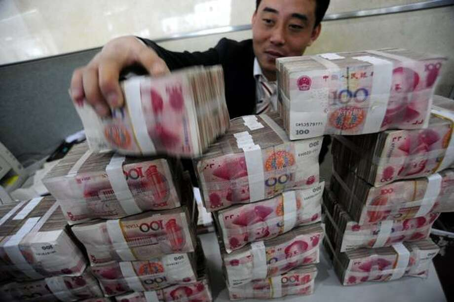 In this Nov. 17, 2009, file photo, a bank clerk stacks up renminbi banknotes at a bank in Hefei in central China's Anhui province. China's central bank promised Saturday to allow more exchange rate flexibility, suggesting a possible break from the Chinese yuan's two-year peg to the U.S. dollar, but it ruled out any large-scale appreciation. Photo: ASSOCIATED PRESS / CHINATOPIX