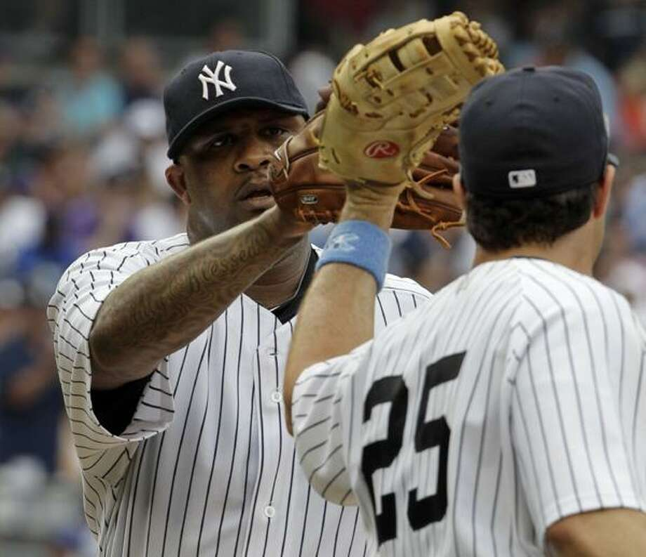 New York Yankees first baseman Mark Teixeira, right, congratulates starting pitcher CC Sabathia, left, after Sabathia pitched out of a jam in the top of the seventh inning of their baseball game against the New York Mets at Yankee Stadium in New York, Sunday. (AP) Photo: ASSOCIATED PRESS / AP
