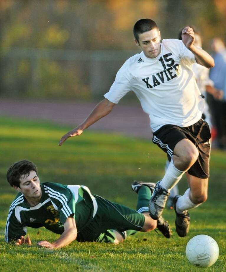 Xavier senior forward Steve Charton battles for posession with Hamden junior midfielder Connor Walsh during a home match for the Falcons. Hamden defeated Xavier 1-0. (Catherine Avalone / TheMiddletownPress