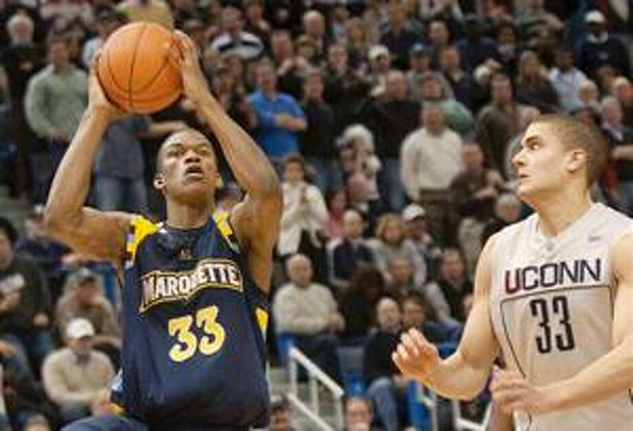 (AP) Marquette's Jimmy Butler, left, shoots the go-ahead basket in the closing seconds of Saturday's game as UConn's Gavin Edwards defends. Photo: AP / FR170131 AP