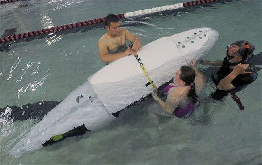 "In this Tuesday, May 31, photo, Old Saybrook High School students Jared Arcari, left, 18, a senior, and Jade Spitale, center, 17, a junior, work with former Navy diver Roy Manstan as they test their one-person submarine ""Miss Jesse Too,"" in the pool at the East Lyme Aquatic & Fitness Center at East Lyme High School. The students plan to race in the International Sub Races. (AP Photo/The Day, Tim Martin) Photo: AP / The Day Publishing Company"