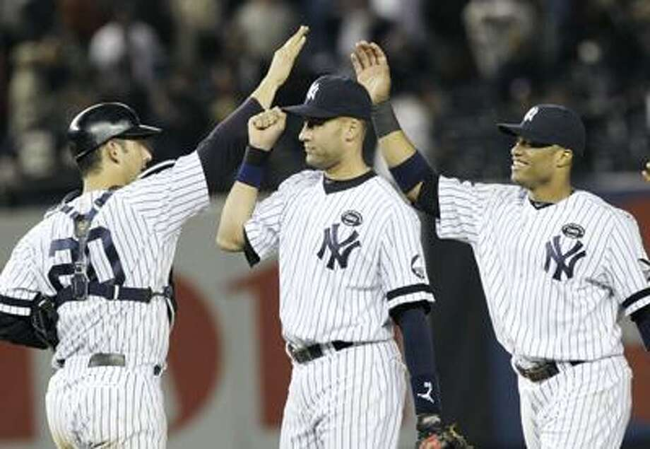 New York Yankees' Jorge Posada (20), Derek Jeter, center, and Robinson Cano celebrate after beating the Texas Rangers 7-2 in Game 5 of baseball's American League Championship Series Wednesday. (AP) Photo: ASSOCIATED PRESS / AP