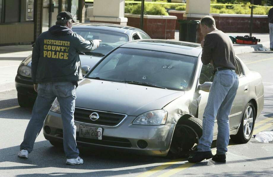 In this photo taken Sunday, Oct. 17, 2010, police look at multiple bullet holes in the windshield of the car driven by Pace University student Danroy Henry outside a restaurant in Thornwood, N.Y. Henry was shot and killed by police earlier in the day as he attempted to drive away from the restaurant. (AP Photo/Seth Harrison, The Journal News) MANDATORY CREDIT, NEW YORK METRO OUT, TV OUT, MAGS OUT, NO SALES Photo: AP / none
