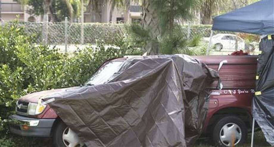 A truck, covered by police, is parked on the side of  I-95 near West Palm Beach, Fla. Wednesday, Feb. 16, 2011, after officials discovered it was filled with chemicals and a body.  A 10-year-old girl whose badly deteriorated body was discovered in her father's pesticide truck is the twin of a boy discovered hours earlier in the vehicle, critically injured after being doused in acid by his father, an official said Wednesday. The pickup truck was found Monday along the side of Interstate 95. But because of the toxic fumes, the girl's body wasn't located until hours later, wrapped in plastic bags, wedged between chemical containers in the pickup truck's bed, according to the official familiar with the children's case.  (AP Photo/J Pat Carter) Photo: AP / AP