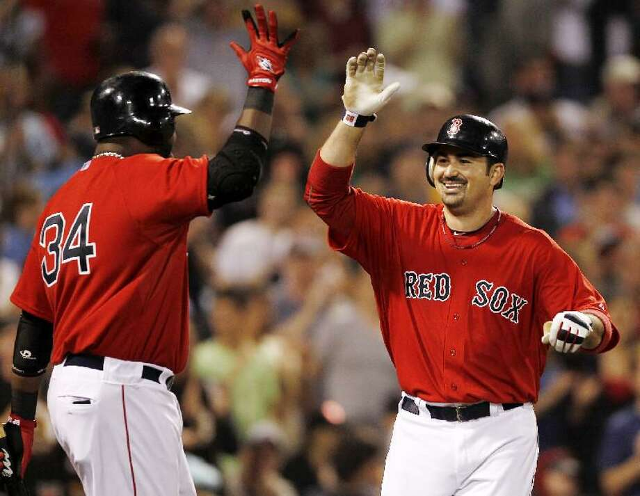 ASSOCIATED PRESS Boston Red Sox first baseman Adrian Gonzalez is greeted by teammate David Ortiz (34) after his solo home run during the fifth inning of Friday's game against the Milwaukee Brewers at Fenway Park.