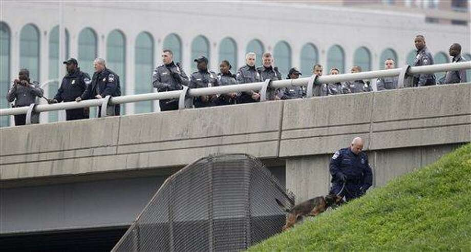 Law Enforcement Officers search for evidence along the  I-395 expressway adjacent to the Pentagon, Tuesday, Oct. 19, 2010. The Pentagon entrances were locked down early Tuesday after a report of possible shots fired near the building. (AP Photo/Pablo Martinez Monsivais) Photo: AP / AP