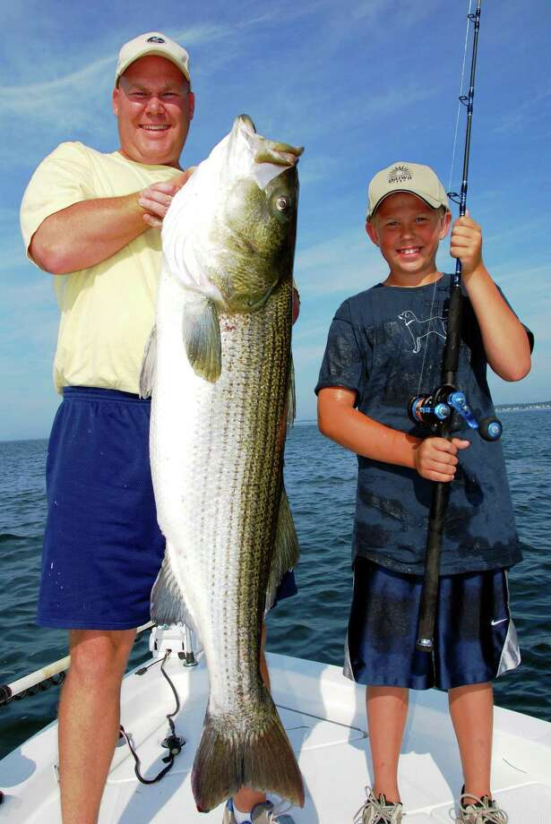 Alan Guild Jr., of Kensington, with his father show off a striped bass that's 52 inches long, weighing 55 pounds.