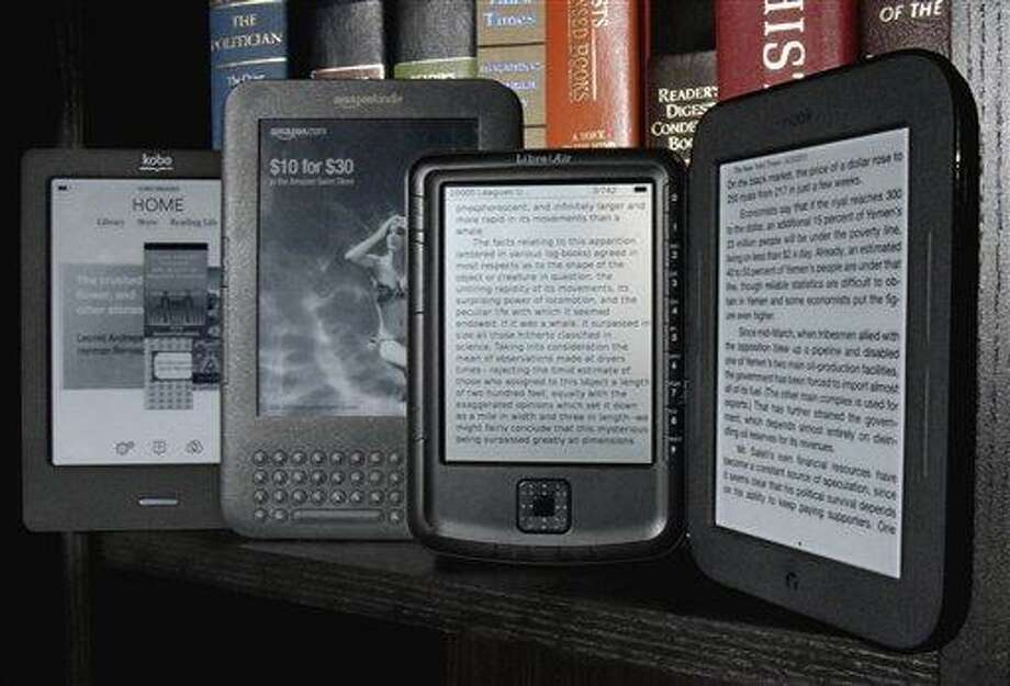 The Kobo eReader Touch, an Amazon Kindle, an Aluratek Libre Air, and a Barnes & Noble Nook, left to right, are displayed in this photo, in New York, Tuesday. When the Kindle was new, in 2007, it cost $399. Now, e-book readers, including a Kindle, can be had for just north of $100. (AP Photo/Richard Drew) Photo: AP / AP