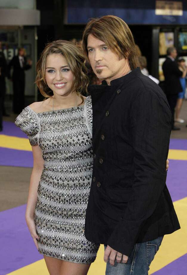 """In this April 23, 2009 photo, singer and actress Miley Cyrus, left and her father musician Billy Ray Cyrus,  arrive during happier days, for the British Premiere of the film """"Hannah Montana"""", at a Leicester Square cinema, in London. (AP Photo/Joel Ryan, file) Photo: ASSOCIATED PRESS / AP2009"""
