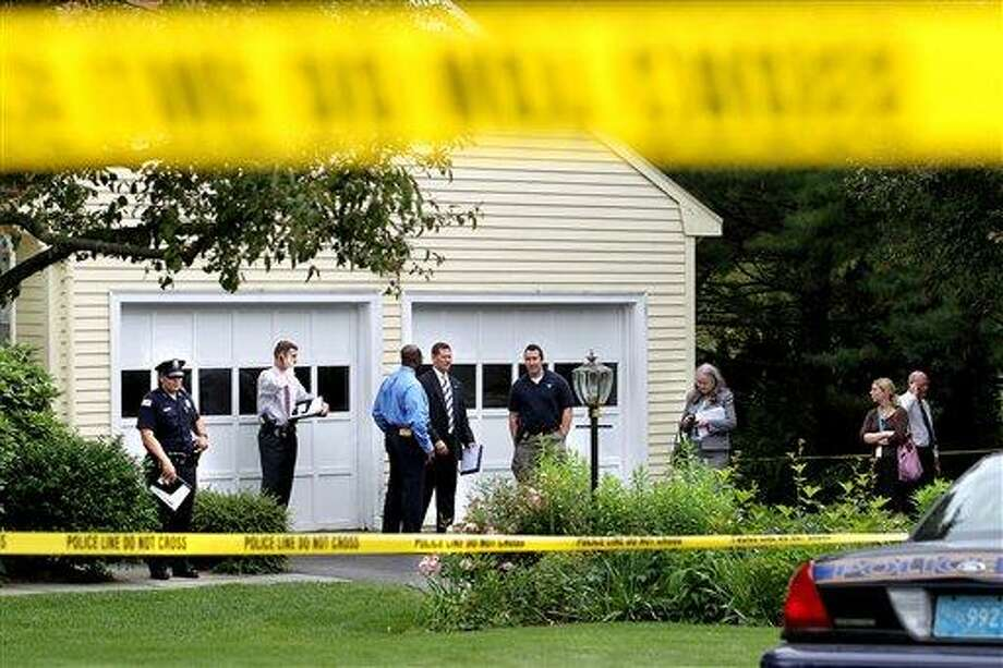 (AP) Officials with the Massachusetts State Police, Winchester Police and the office of Middlesex District Attorney Jerry Leone, fourth from left, conduct an investigation into the deaths at a home in Winchester, Mass. on Wednesday. Police are seeking a person for questioning after four people were found dead at suburban home north of Boston. Photo: AP / The Boston Globe