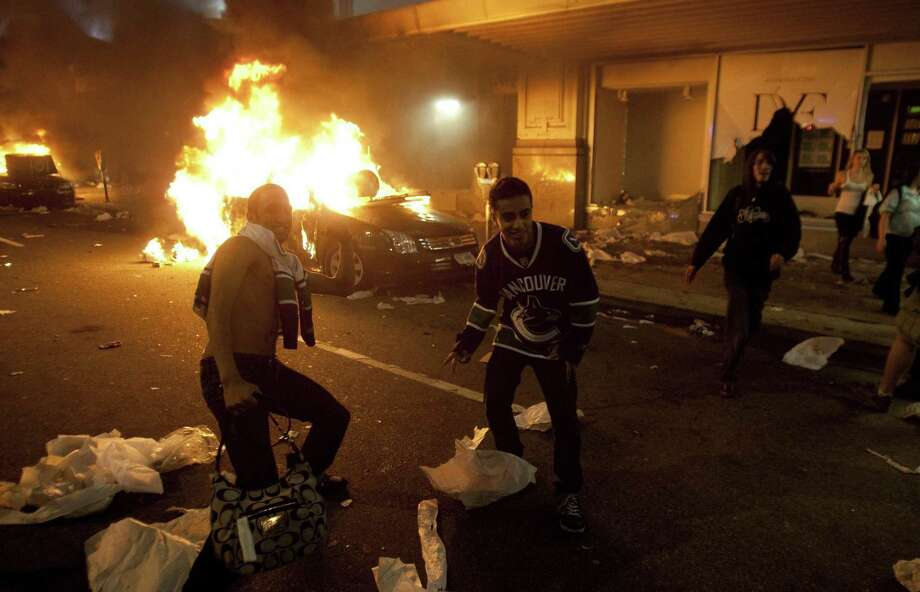 Vancouver Canucks hockey fans take part in a riot in downtown Vancouver, Canada, Wednesday, June 15, 2011, following the Vancouver Canucks 4-0 loss to the Boston Bruins in game 7 of the Stanley Cup hockey final. Angry, drunken revelers ran wild Wednesday night after their team's loss, setting cars and garbage cans ablaze, smashing windows, showering giant TV screens with beer bottles and dancing atop overturned vehicles. (AP Photo/The Canadian Press, Ryan Remiorz) Photo: ASSOCIATED PRESS / AP2011