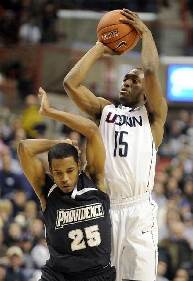 AP Connecticut's Kemba Walker fakes a shot over Providence's Bryce Cotton during the second half of Connecticut's 75-57 victory in their NCAA college basketball game in Storrs on Sunday. Walker scored 22 points and had six rebounds in the win.