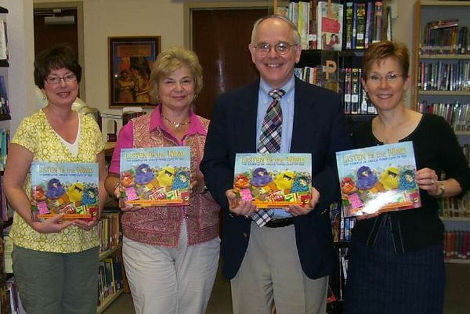 """From left to right, Peggy Schaedler, DRES library media specialist, Deep River Rotarian Gail Onofrio, Deep River Elementary School Principal Dr. Jack Pietrick and school social worker Laura Kasprow are seen holding copies of """"Listen to the Wind."""" The Rotary Club of Deep River donated 21 copies of the book to Deep River Elementary School. (Submitted photo)"""