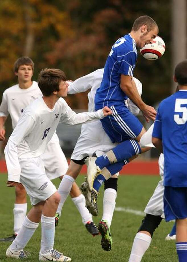 East Hampton's Stephan Marsiglio, center, wins a header in a crowd against Westbrook Monday. East Hampton won 4-0. (Todd Kalif