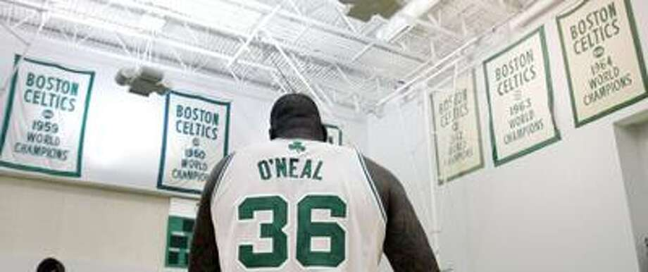 Boston Celtics center Shaquille O'Neal walks under the NBA Championship banners during their media day at the team's NBA basketball training camp in Waltham, Mass., Monday, Sept. 27. (AP) Photo: ASSOCIATED PRESS / AP