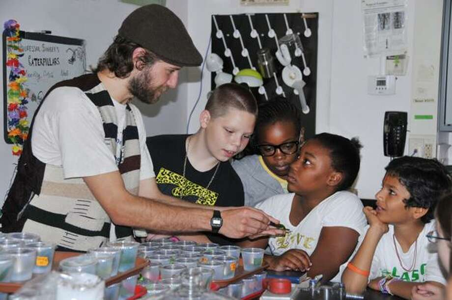 Wesleyan University senior Isaac Lichter-Marck shows an eastern tiger swallowtail caterpillar to fifth grade students from Snow Elementary School on June 16. The students are, from left, Logan Daniels, Shaianah Dempsey, Ardejah Hayes and Harish Patel.