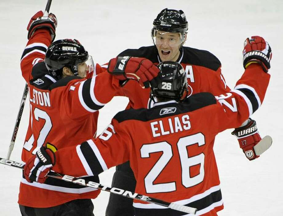 New Jersey Devils' Ilya Kovalchuk, of Russia, Brian Rolston, left, and Patrik Elias (26), of the Czech Republic, celebrate a goal by Rolston during the third period of an NHL hockey game against the San Jose Sharks Friday, Feb. 11, 2011 in Newark, N.J. The Devils defeated the Sharks 2-1. (AP Photo/Bill Kostroun)